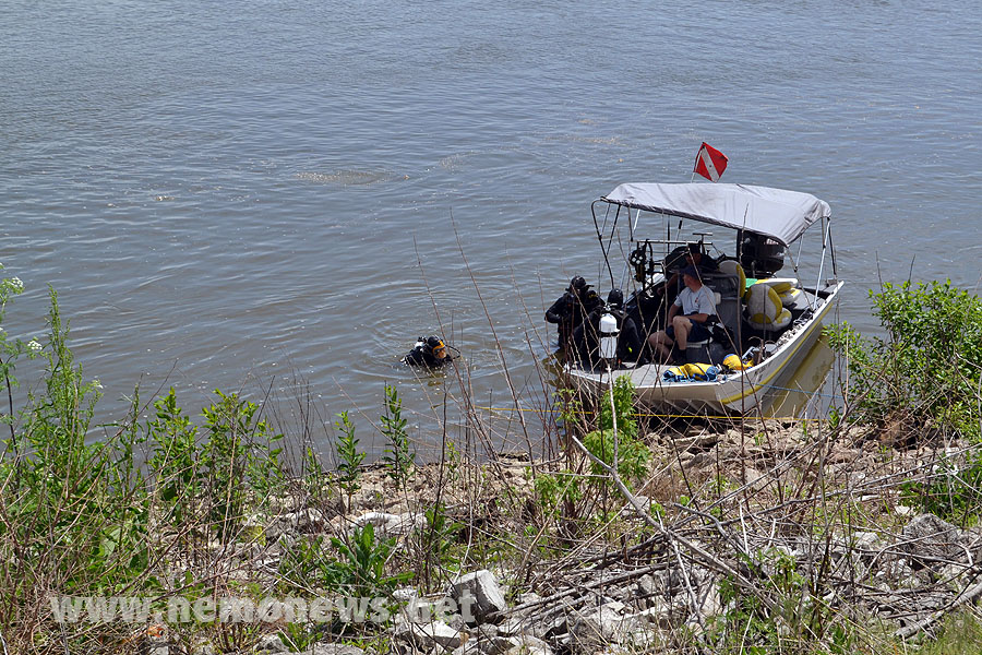 A diver prepares to take the tow line to the submerged vehicle