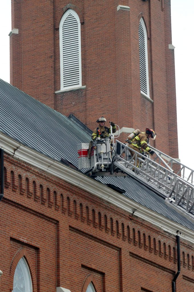 Firefighters enter church roof opening to battle blaze.