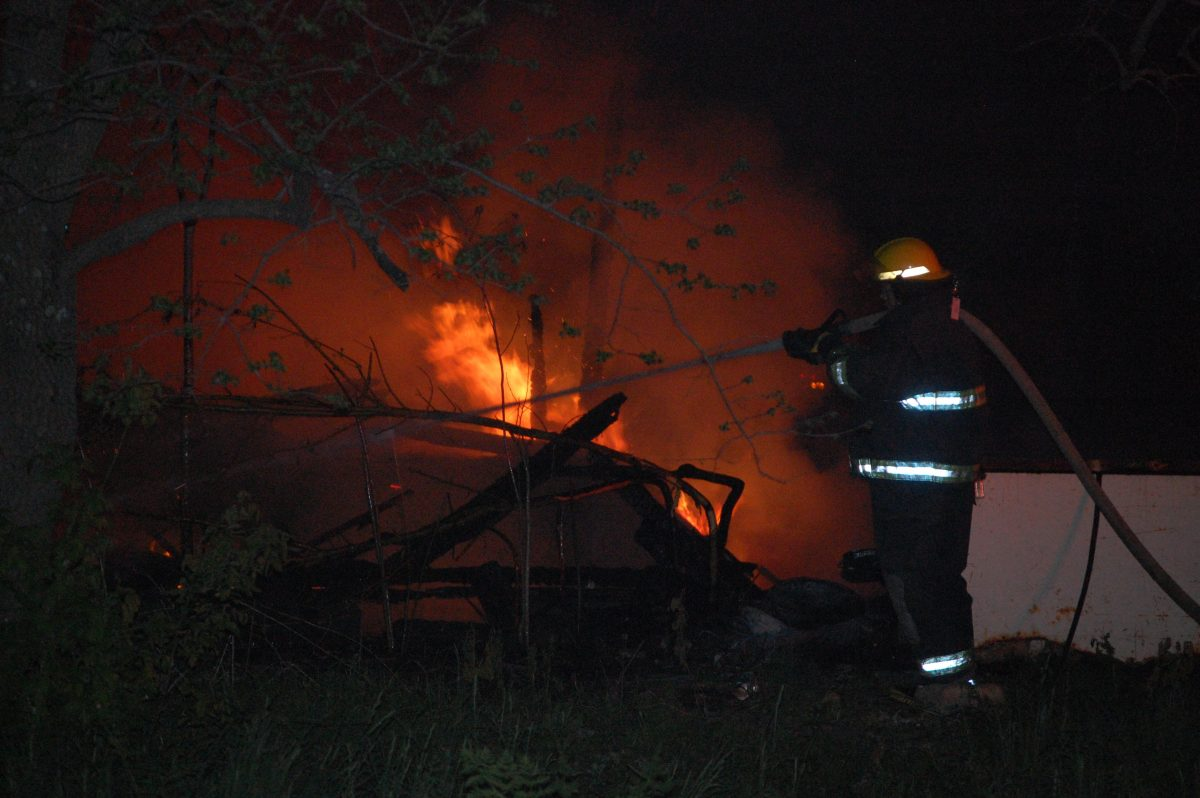 A Wayland firefighter puts water on the burning structure in Winchester on Sunday night.