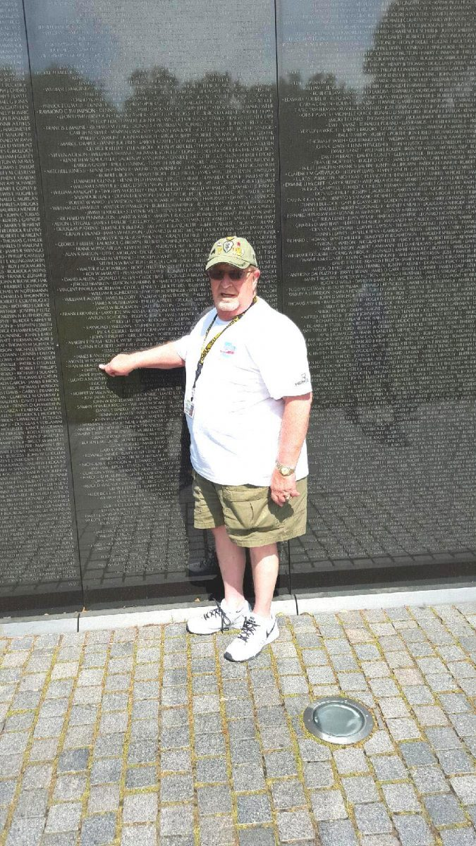 Rodney Smith points to the name of his school friend (Jean M. Kraus) whose name appears on the Vietnam Memorial Wall in Washington D.C. Rodney left a basketball photo of the two taken while they were in school together.