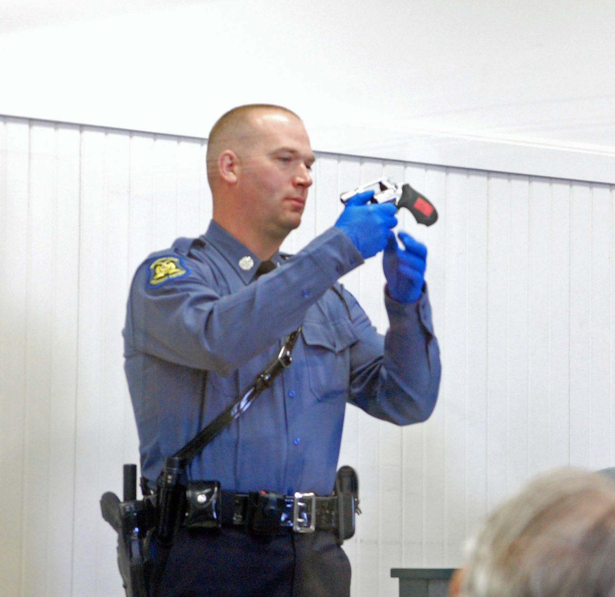 Trooper Craig Reichert shows the gun Glenn Head used to shoot Bill Bacon.
