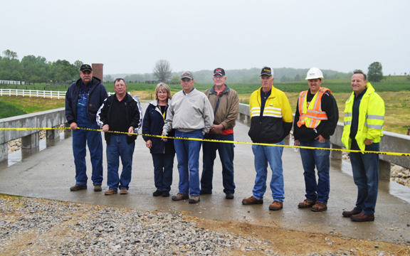 Ribbon Cutting--The new bridge on County Rd. 62 opened Thursday morning. Pictured are former Presiding Commissioner Ron Brewer, Western Commissioner Paul Brotherton, Barbara and Paul O'Day, Eastern Commissioner Henry Dienst, Presiding Commissoner Buddy Kattelmann, and representatives from MoDOT and Chester Bross Construction
